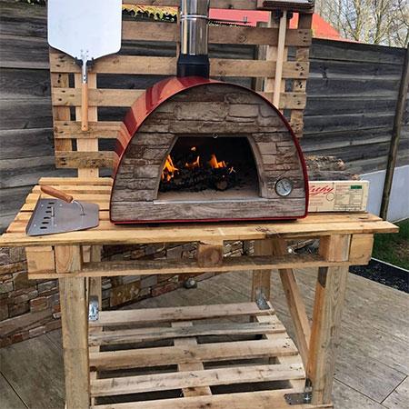 cuisson d'une pizza au feu de bois avec un four extérieur