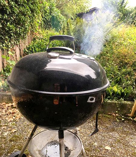 grill weber pour saucisse qui dégage de la fumée