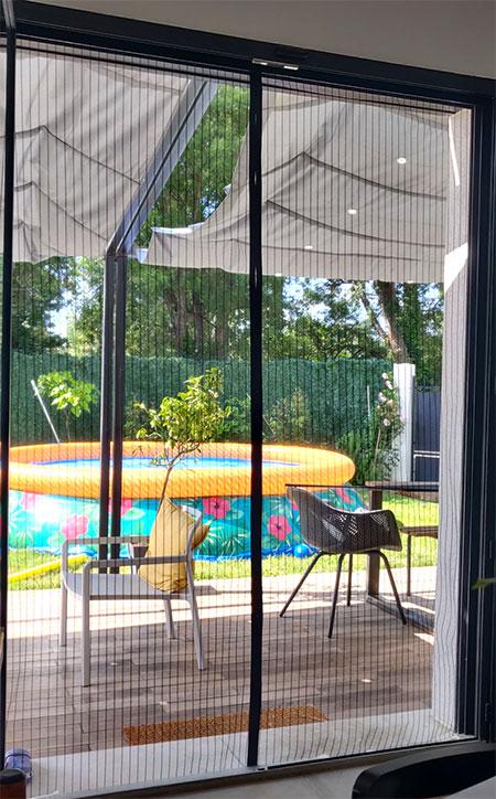 moustiquaire pour baie vitrée face à un jardin