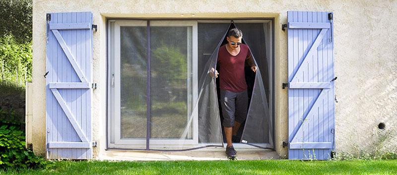 homme traversant une moustiquaire de baie vitrée