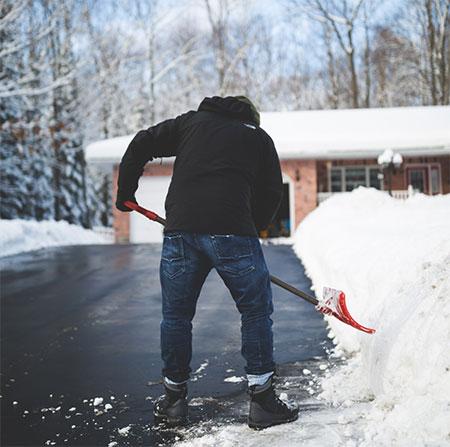 homme en train de pelleter la neige
